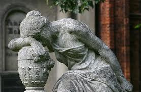 Thsi is a statue of a distressed woman draped over an urn, head in hand